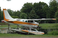 Pontoon Plane. A pontoon plane parked on the side of a lake stock photo