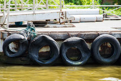 Pontoon with recycled old tyres used as boat bumpers. Royalty Free Stock Photography