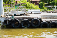 Pontoon with recycled old tyres used as boat bumpers. Stock Photo