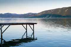 Pontoon on river shore. Wooden deck on Danube river shore with mountains on background at sunset Royalty Free Stock Photography