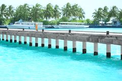 Pontoon at sea resort and blurred berthed boats. On background royalty free stock photo