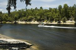 Pontoon on Suwannee River. A pontoon glides by on the Suwannee River Stock Photography