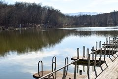 Pontoon wooden jetty pier for boat mooring marina on the park lake.  royalty free stock photography