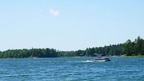 Pontoons on a beautiful lake in northern Minnesota with blue sky and fluffy clouds. Boating in Minnesota,. Land of 10000 Lakes stock footage