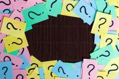 Pontos de interrogação coloridos dos bilhetes escritos fundo dos lembretes do quadro peça ou conceito do negócio com espaço da có Fotografia de Stock