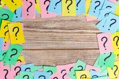 Pontos de interrogação coloridos dos bilhetes escritos fundo dos lembretes do quadro peça ou conceito do negócio com espaço da có Foto de Stock