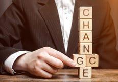 Pontos do homem de negócios aos blocos de madeira com a mudança da palavra à possibilidade Desenvolvimento pessoal Crescimento da imagem de stock royalty free