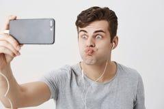 Ponura caucasian samiec marszczy brwi twarz, trzyma mądrze telefon w jego ręce, patrzeje kamerę z strzelającymi oczami, pouting w Obraz Royalty Free