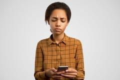 Ponuractwo wzburzona dziewczyna robi grymasowi od rozpacza, trzyma smartphone, czyta disapponting wiadomość, patrzeje oklapniętą zdjęcia stock