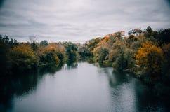 Ponury niebo, rzeka i jesieni drzewa, Fotografia Stock