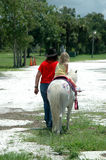 Pony ride. A little blonde girl led on a pony ride at the fair Royalty Free Stock Image