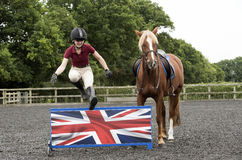 Pony rider jumping a low fence Royalty Free Stock Images