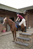 Pony rider using a mounting block. Young rider using a mounting block - September 2016 - Teenager using the steps on a mounting block to get into the saddle of Royalty Free Stock Photography
