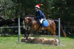 Ponyreiter, der mit Vater-Christmas-Hut springt Stockfotografie