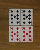 Pookkaarten op een houten backround, reeks nines van clubs, diamanten, spades, en harten royalty-vrije stock foto's