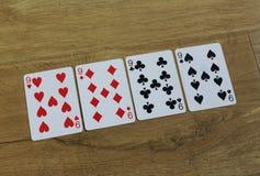 Pookkaarten op een houten backround, reeks nines van clubs, diamanten, spades, en harten stock afbeelding