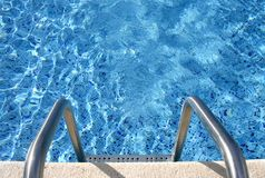 Into the pool. Ladder leading into the swimming pool Royalty Free Stock Photos