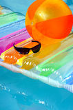 In the pool. Airbed,ball,and sunglasses in the pool stock photo