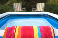 By the pool. Seats and towel by the pool royalty free stock photography