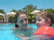 In the pool. Mother with little girl in the pool stock image