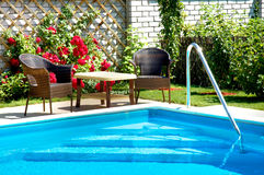 Pool. With lounge area and garden patio furniture Royalty Free Stock Images