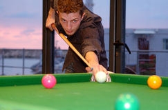 Pool. Young man playing pool,with sunset in the background royalty free stock image