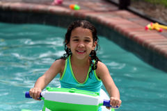 In The Pool. A young girl rides a boat Stock Image