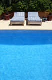 By the pool. Two beds close to a swimming pool Stock Image