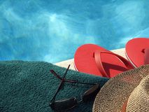By the Pool. Shot of a towel, sunglasses, hat and sandals by the pool stock photography