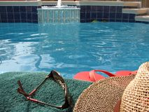 By the Pool. Shot of a towel, sunglasses, hat and sandals by the pool royalty free stock photo