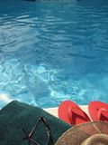 By the Pool. Shot of a towel, sunglasses, hat and sandals by the pool royalty free stock image