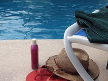 By the Pool. Shot of a towel, sunglasses, hat, suntan lotion, beach chair, and sandals by the pool stock photo
