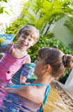 In pool. Portrait of young attractive woman having good time with her daughter Royalty Free Stock Photo