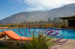 Colored loungers by the pool. Pool against the backdrop of the mountains. orange sun loungers. white towels stock image
