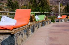 Colored loungers by the pool stock photo