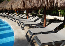 Pool amenities on a Caribbean resort. Straw umbrellas and folding chairs around a pool in a Caribbean beach resort in Riviera Maya, Mexico royalty free stock photography