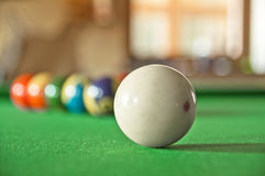 Pool balls. White pool ball with 10 balls in the background on a green table Stock Images