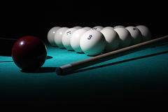 Pool balls. Under a light beam. The ball pyramid with the number 8 ball on the  foreground. Low-key scene Stock Photo