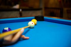 Pool balls on the blue felt pool table with player hands and pool cue stick. Indoor sports. sport and gambling concept. Image for background, copy space and Royalty Free Stock Image