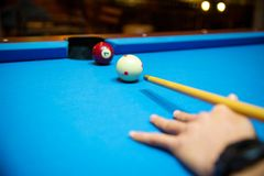 Pool balls on the blue felt pool table with player hands and pool cue stick. Indoor sports. sport and gambling concept. Image for background, copy space and Stock Photography