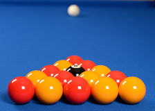 Pool balls on blue table. Red and yellow pool balls arranged in triangle on blue table with white object ball in background Royalty Free Stock Images