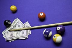 Pool balls and cue with US dollars Royalty Free Stock Photos