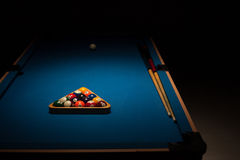 Pool balls and cues on a blue baize table. Pool balls stacked in the triangular rack, the cue ball and cues on a blue baize table in a shadowy dark nightclub royalty free stock photos