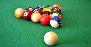Pool balls on green felt. Packed pool balls on a green felt pool table with the white ball in front. Focus is on the colored balls stock photo