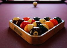 Pool Balls on Table. Pool balls in rack on a pool table with the cue ball in the distance, selective focus Stock Photo