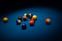 Pool balls scattered on a pool table. Covered in blue baize under an overhead light in a shadowy nightclub or bar Royalty Free Stock Images