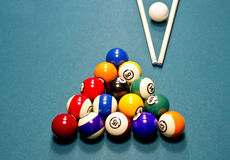 Pool balls on table. Overhead view of pool or billiard balls on baize table with white ball and cues Royalty Free Stock Photos