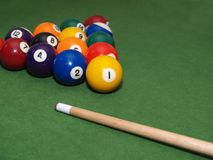 Pool balls on table. Pool balls and stick racked and ready on a billiards table Stock Photography