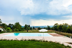 Pool. A beautiful and luxurious tuscany swimming pool with parasols and chairs Stock Photography