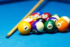 Pool billiard balls and cue on the table Royalty Free Stock Photos